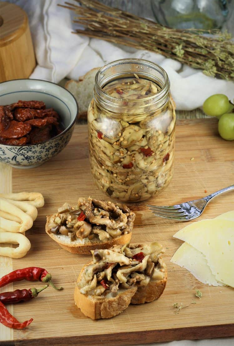 jar of pickled eggplant on wood board with antipasto