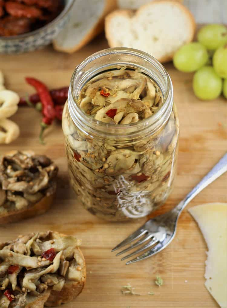 jar of pickled eggplant with fork and crostini around it