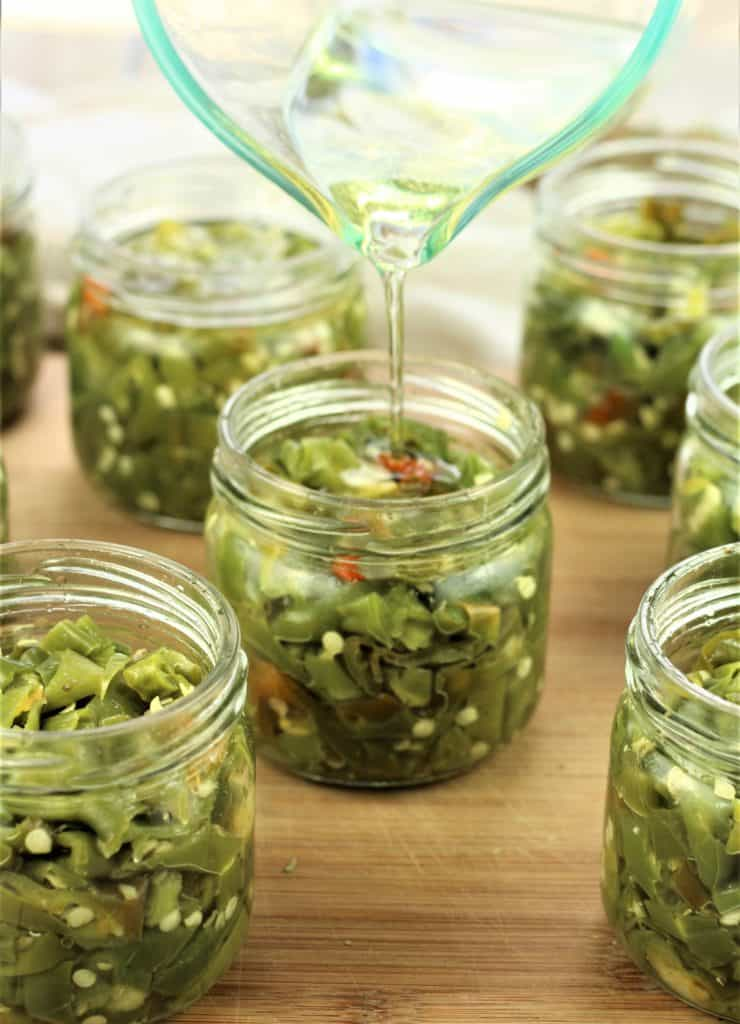 topping off jars with Italian hot pickled peppers with oil