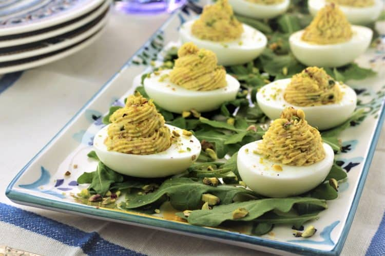 deviled eggs on platter with arugula and chopped pistachios