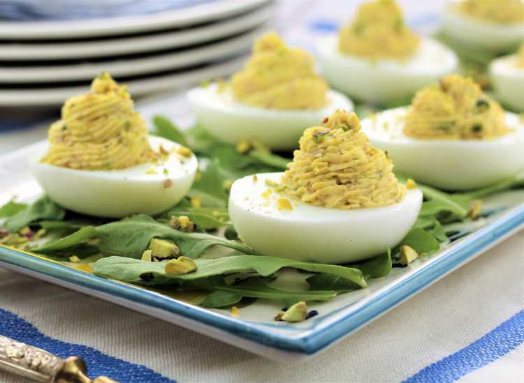 deviled eggs on an arugula covered platter with pistachio pieces