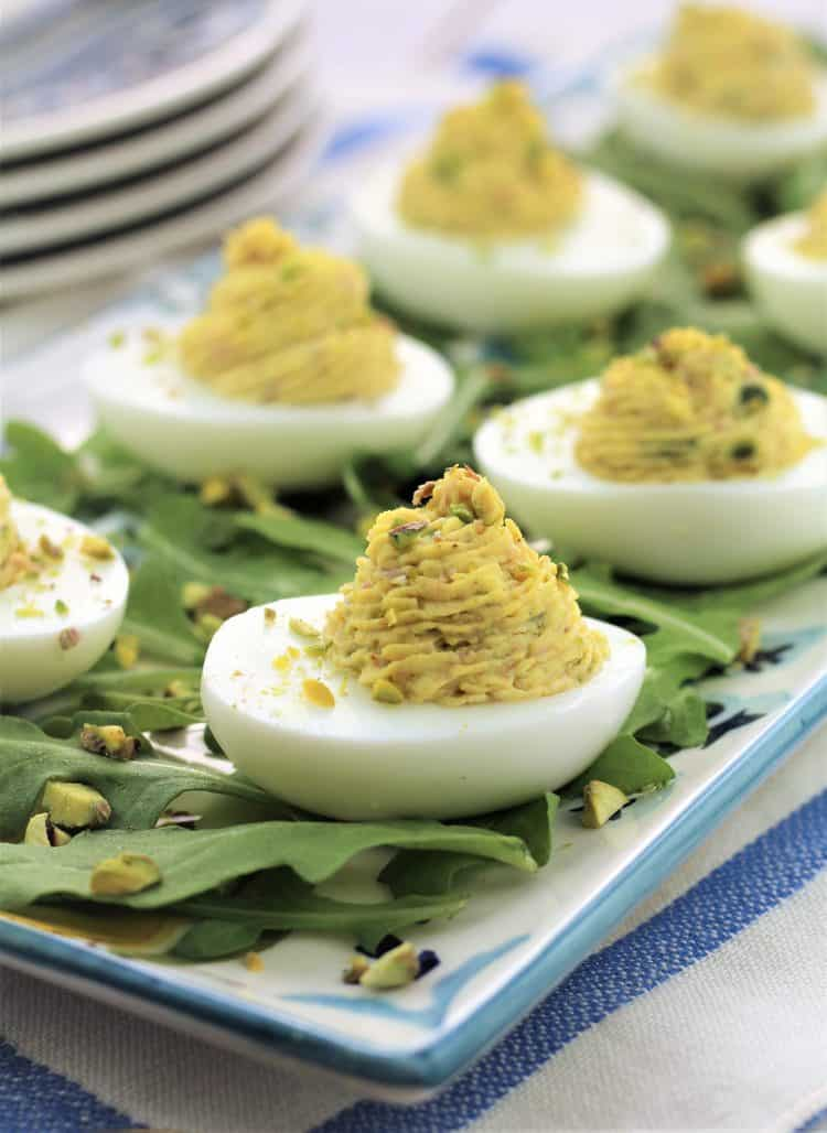 deviled eggs on a rectangular plate covered with arugula leaves and pistachio pieces
