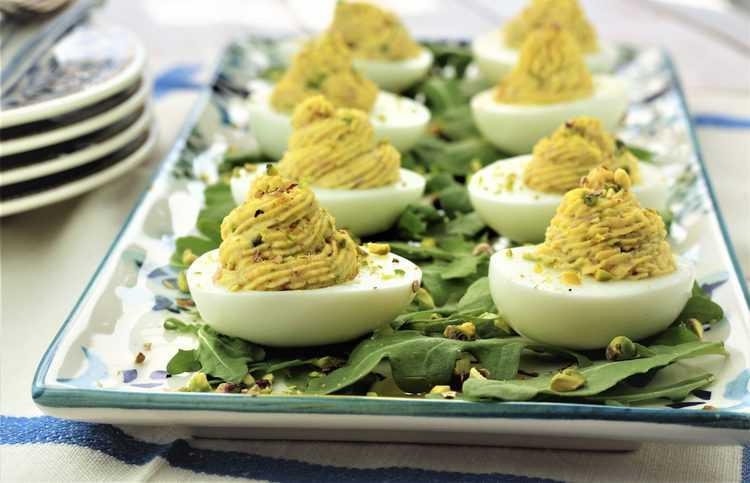 deviled eggs on a rectangular plate covered with arugula leaves and chopped pistachios
