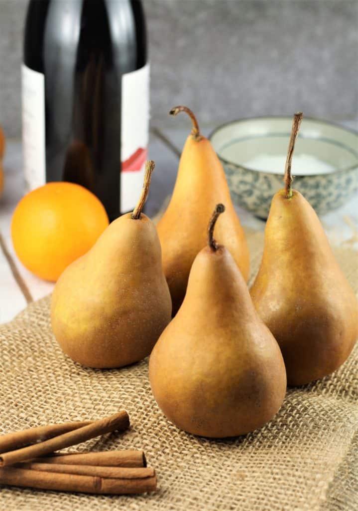 bosc pears, cinnamon sticks, bowl of sugar, orange and bottle of wine