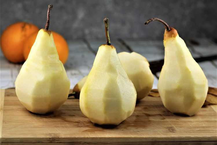 4 peeled Bosc pears on wood board
