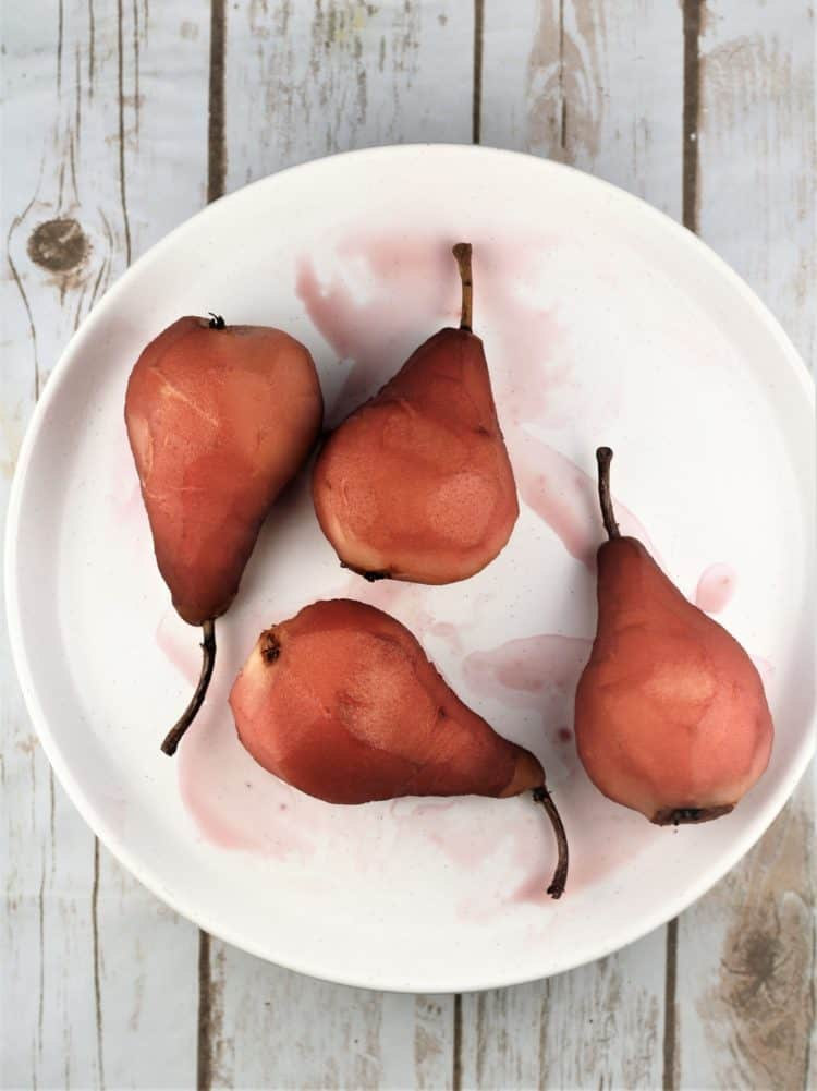 pears poached in red wine on white round plate