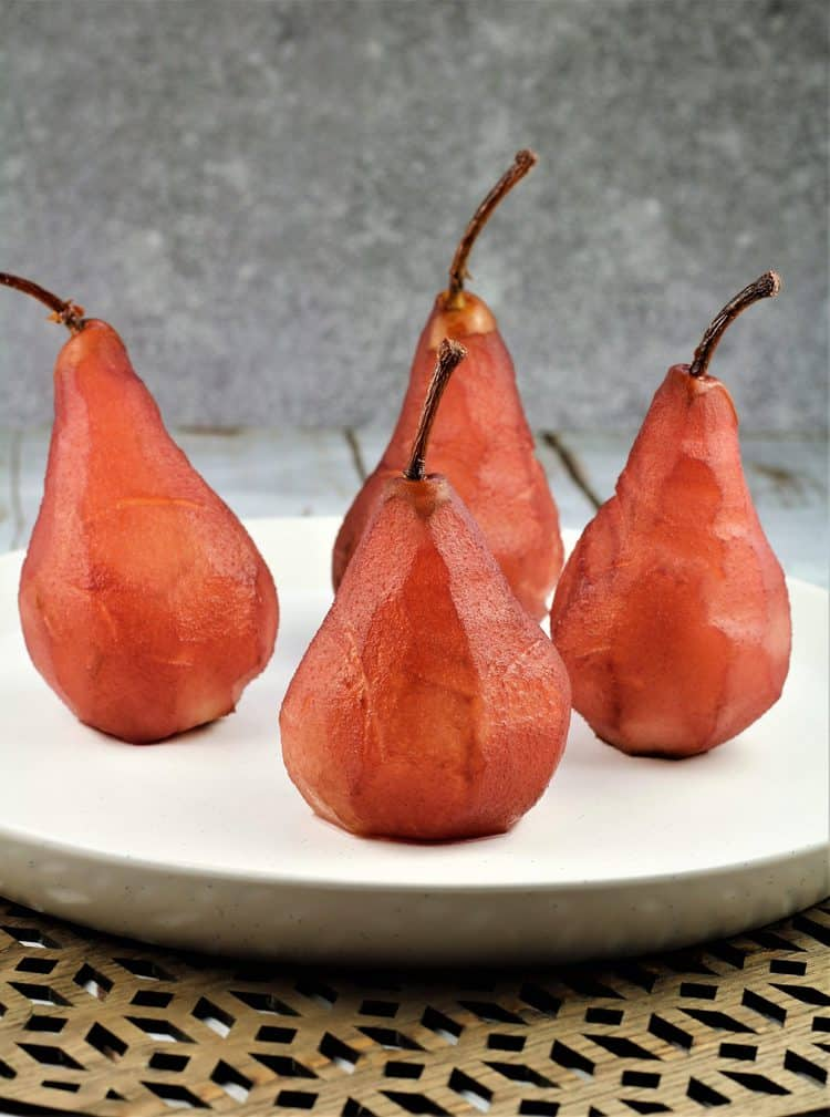 4 red wine poached pears on white round plate