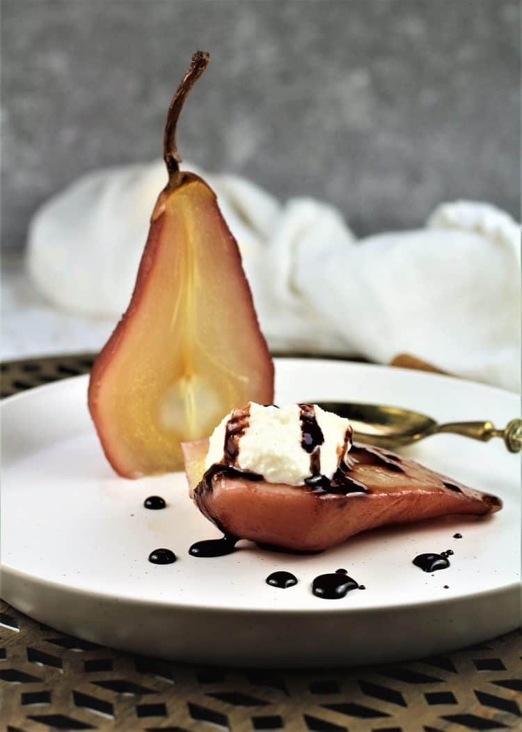 halved poached pear on plate with ricotta dollop in one half drizzled with syrup