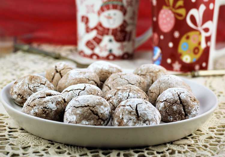 plate of chocolate espresso amaretti with Christmas mugs behind it