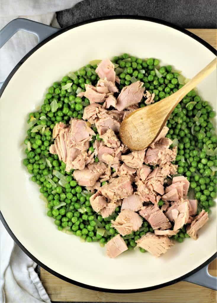 large skillet with green peas and tuna chunks stirred in