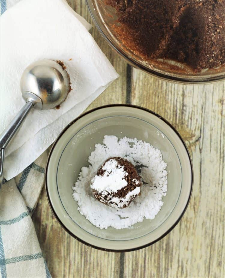 dredging chocolate cookie dough in bowl of powdered sugar