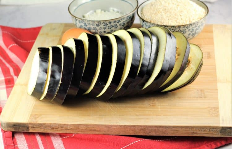sliced globe eggplant on wood board over red dish cloth