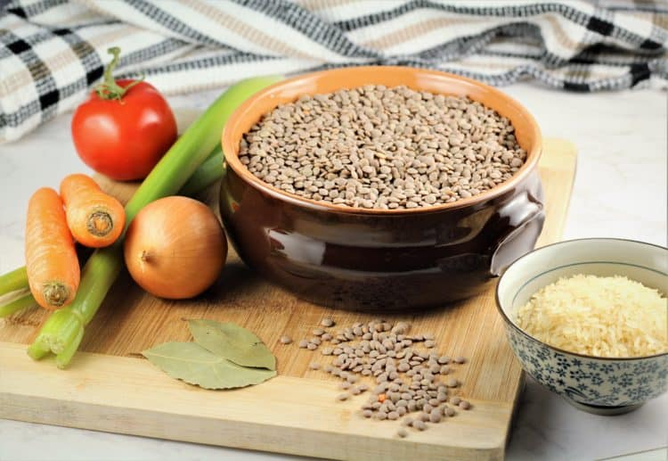 ceramic bowl of brown lentils on wood board with carrots, celery, onion and bowl of rice