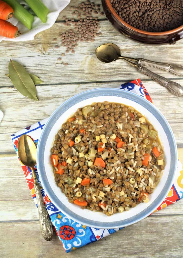 overhead view of lentils with rice in blue rimmed bowl with spoon on side