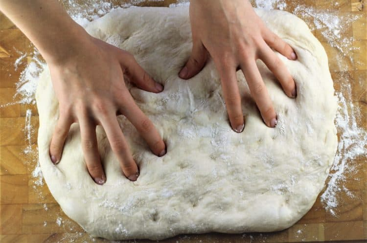 shaping no knead pizza dough with finger tips