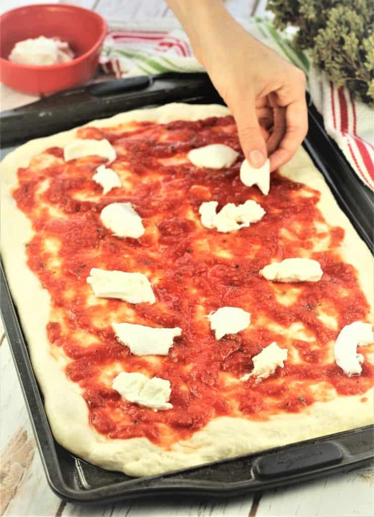 adding mozzarella onto a tomato pizza on baking sheet