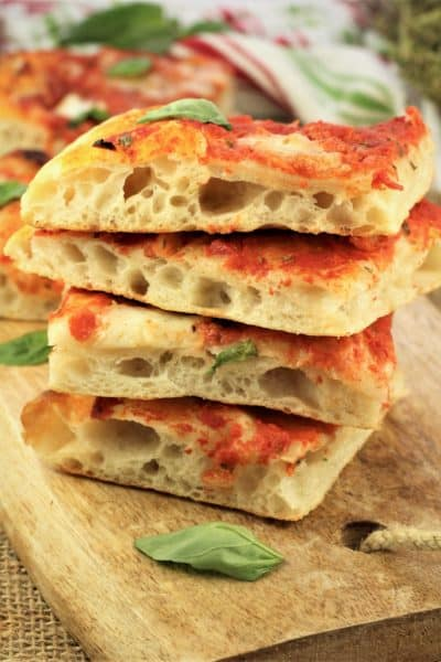 No knead pizza Margherita squares piled on one another on wood serving board