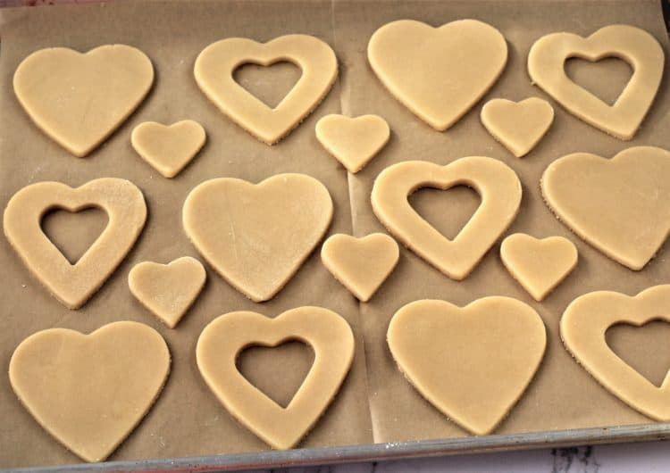 heart cookie dough shapes on parchment paper