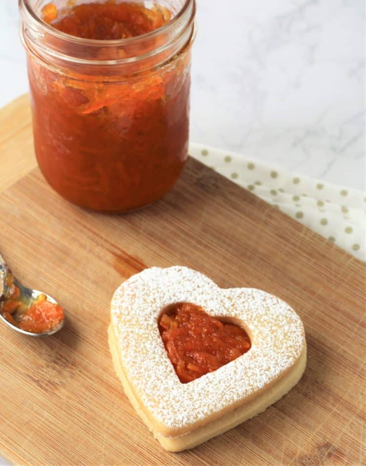 heart cookie filled with jam next to jam jar and spoon
