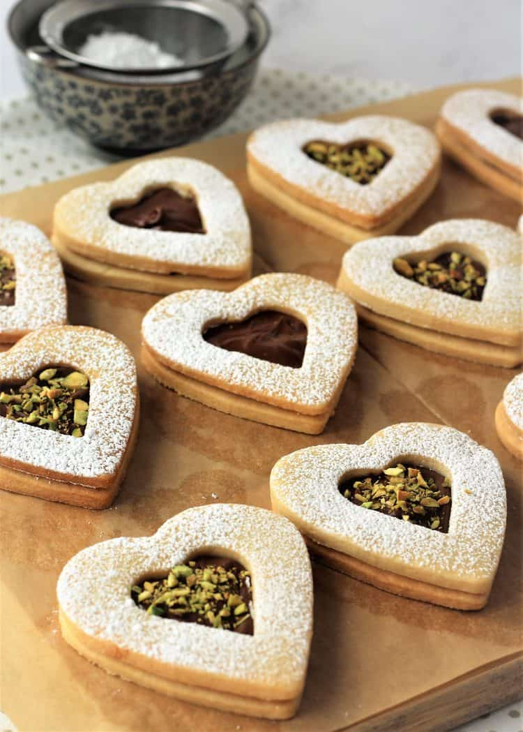 Nutella and pistachio filled heart cookies on parchment paper