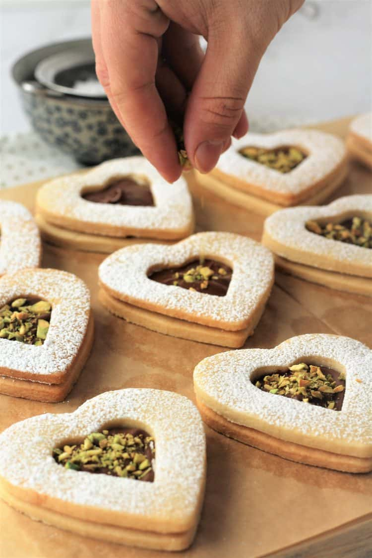 sprinkling toasted pistachios on Nutella filled cookie hearts