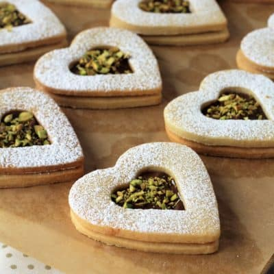 Nutella and pistachio heart cookies on wood board