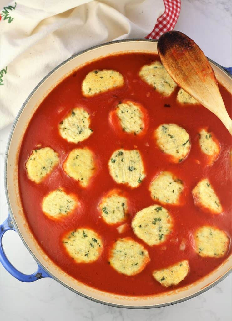 meatless meatballs nestled in tomato sauce in large sauce pan