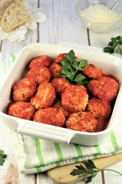 square dish filled with meatless meatballs with sprig of parsley on green striped dishcloth