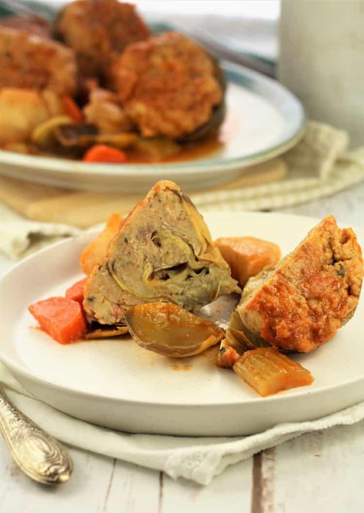 stuffed artichoke cut in half on white plate
