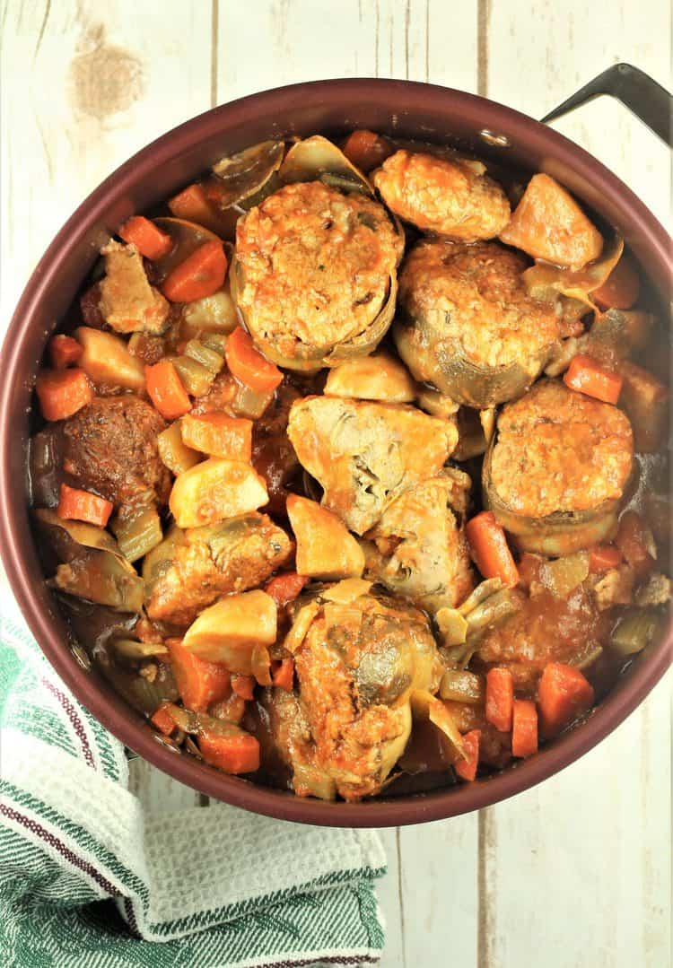 large sauce pan with stewed stuffed artichokes and vegetables