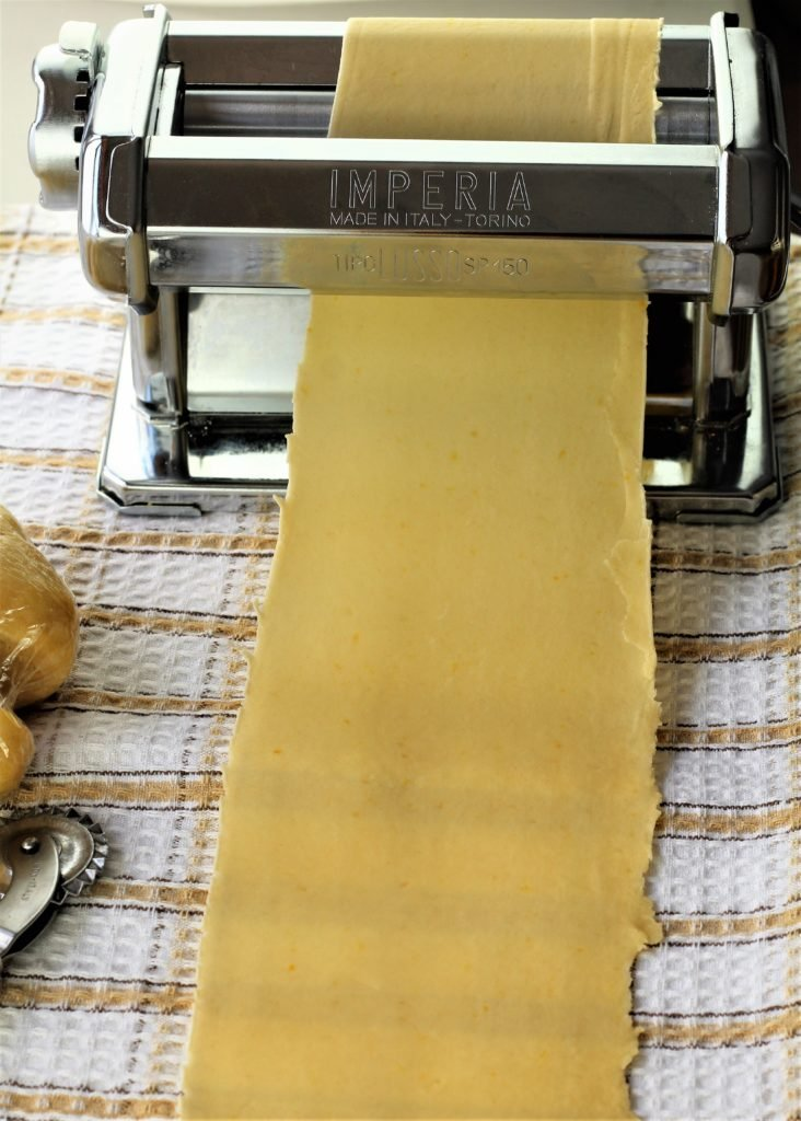 pasta roller shown with sheet of dough rolled