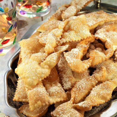 chiacchiere di carnevale piled onto silver tray