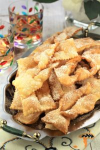 chiacchiere di carnevale strips piled on silver tray