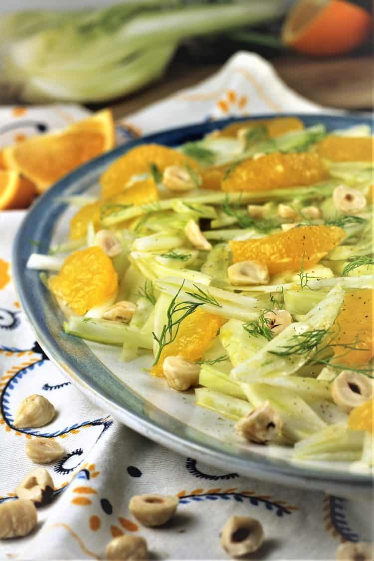 blue rimmed white platter with sliced fennel and orange segments with hazelnuts