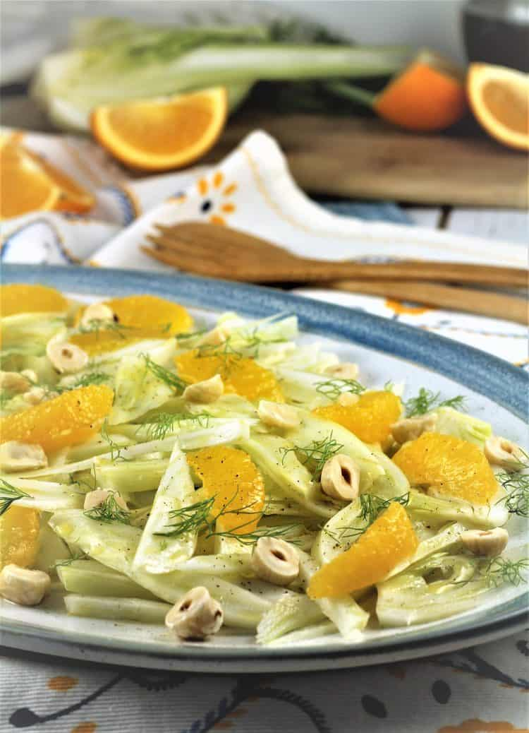 blue rimmed white plate topped with sliced fennel and orange salad with hazelnuts