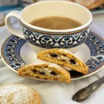 blue and white coffee cup with sweet panelle cookie cut in half on the saucer