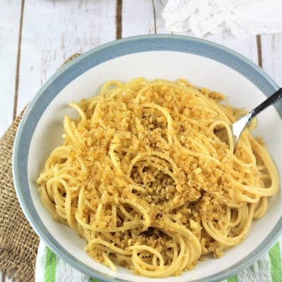 blue rimmed bowl of spaghetti with breadcrumbs with fork in it