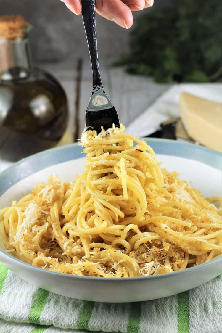 fork twirling around spaghetti with breadcrumbs in pasta bowl