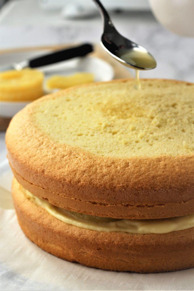 pineapple juice being spooned over sponge cake