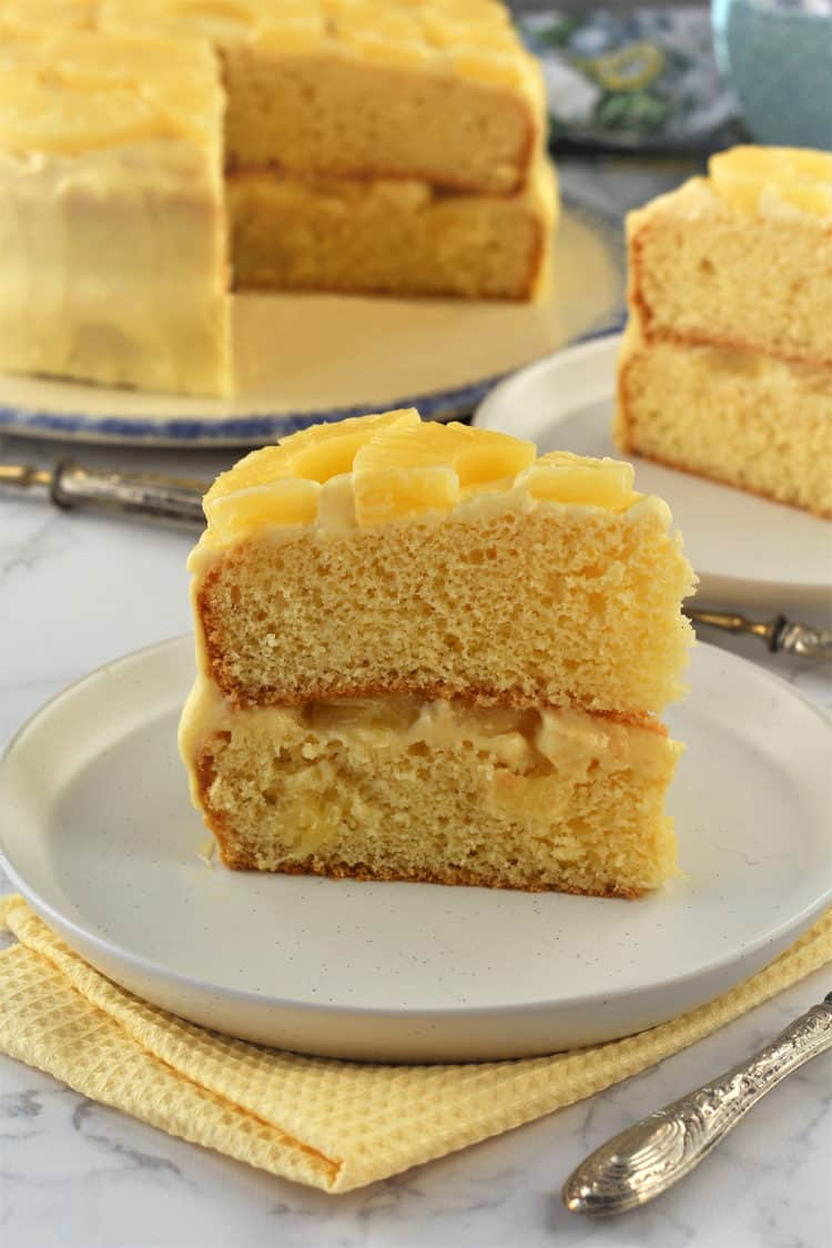 slice of pineapple layer cake with pastry cream on plate with whole cake behind it