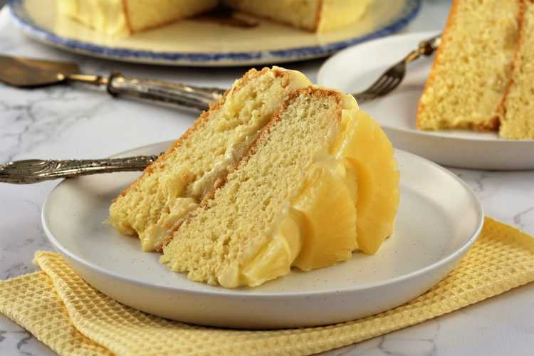slice of sponge cake with pineapple on white plate over yellow napkin