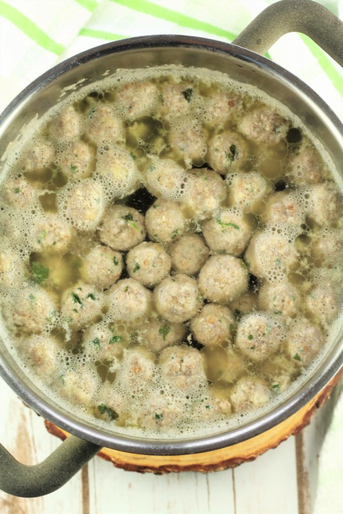 tiny meatballs shown simmering in water in small sauce pan