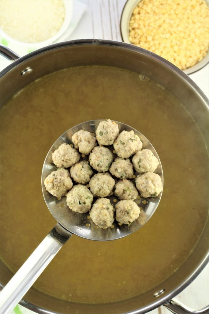 slotted spoon full of small meatballs over pot with broth