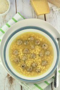 bowl of pastina soup with tiny meatballs with cheese in background