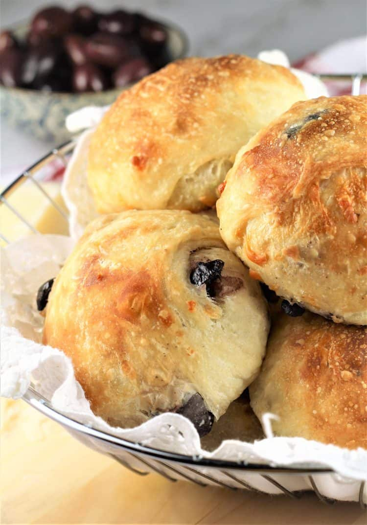olive and cheese buns in bread basket with bowl of olives in background