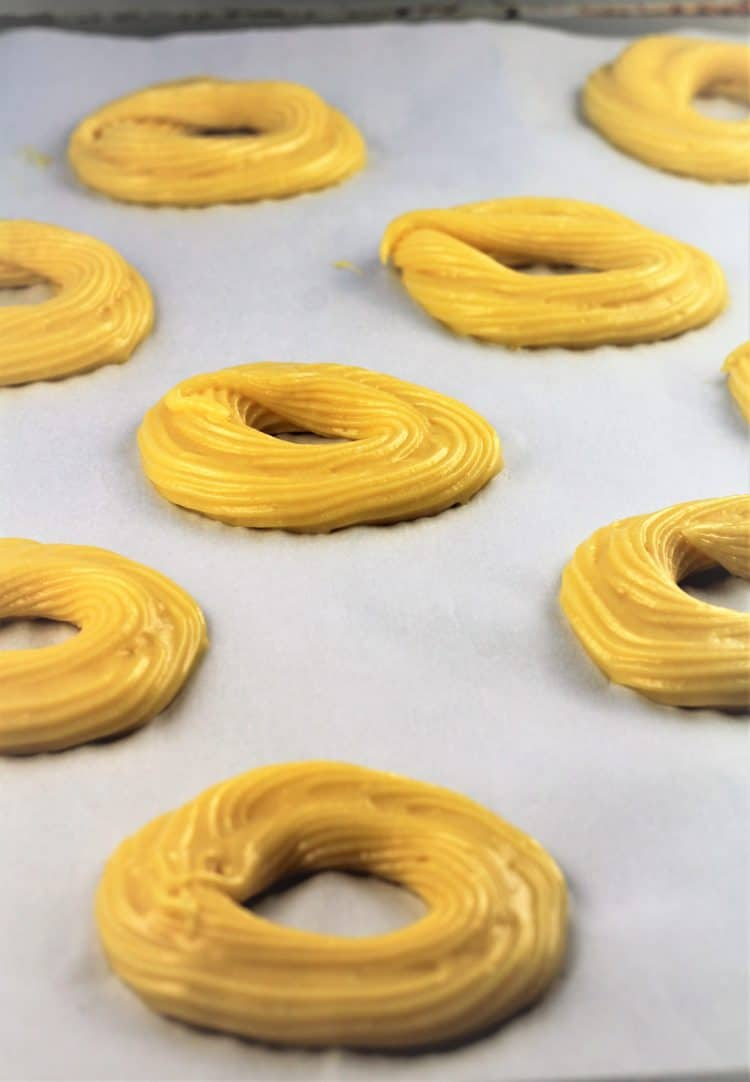 piping choux pastry into rings onto baking sheet