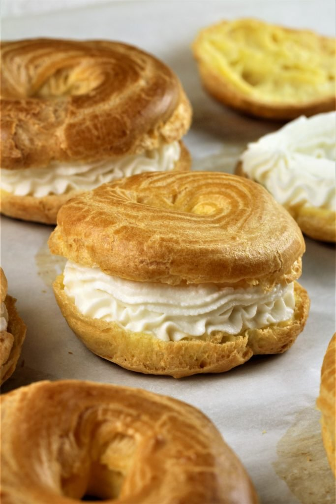 choux pastry filled with ricotta cream on parchment paper with other choux
