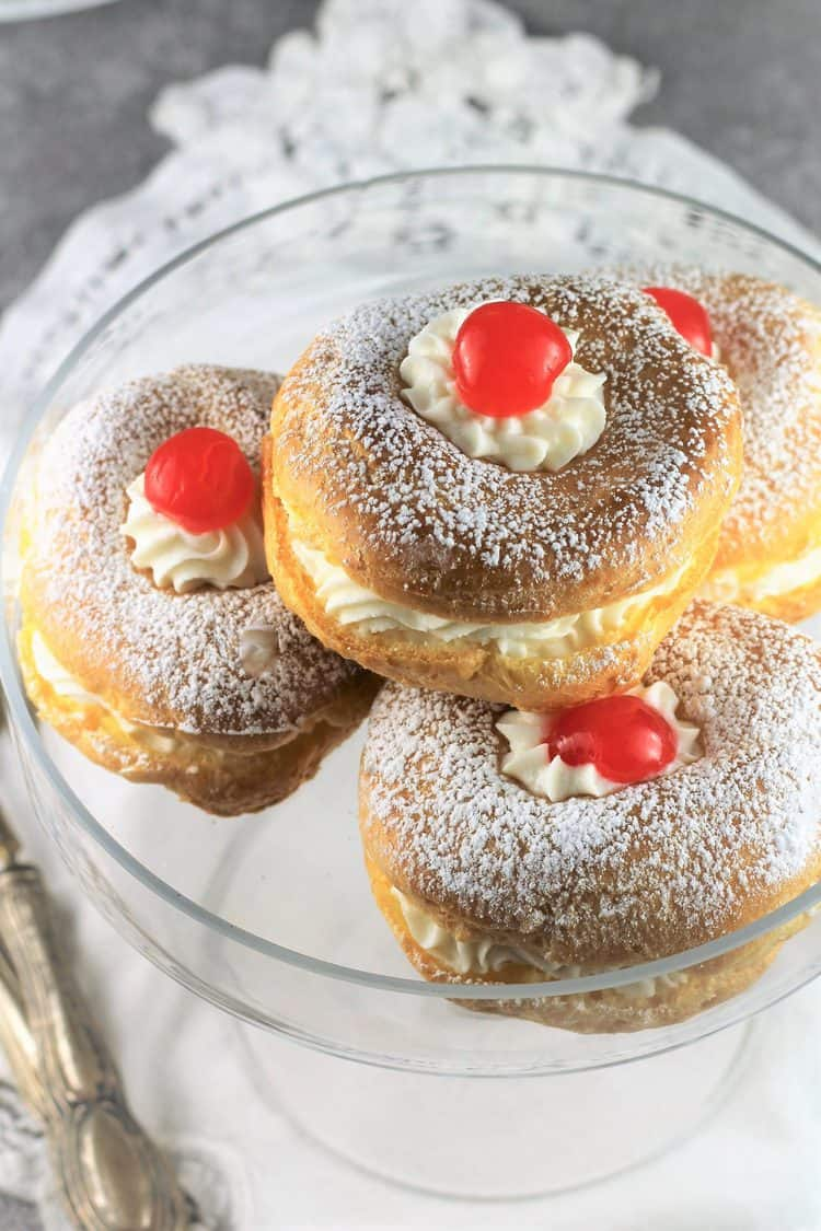 3 zeppole on glass plate with cherries on top