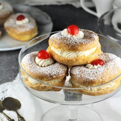 pedestal plate with 3 zeppole filled with ricotta and cherry on top