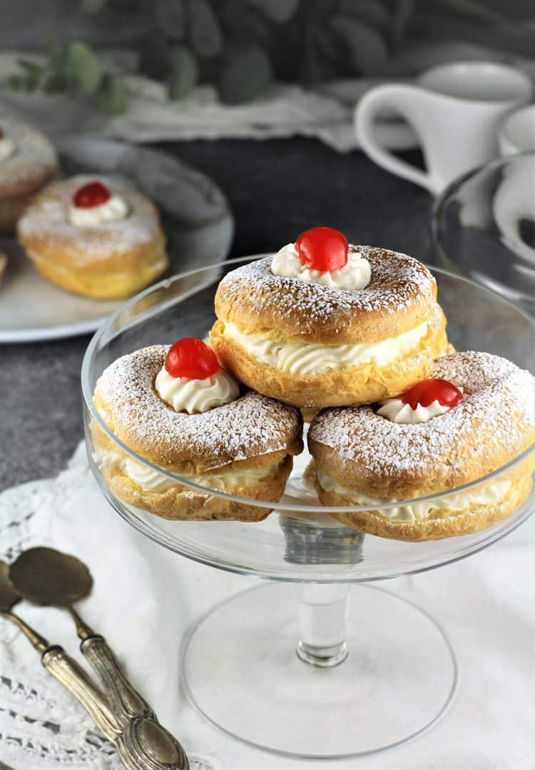 glass pedestal plate with 3 zeppole filled with ricotta for St-Joseph's Day with cherry tops